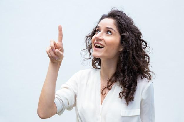 Mulher alegre feliz, apontando o dedo para cima