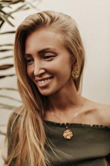 Mulher alegre, feliz, bronzeada, de cabelos compridos, com uma camiseta verde escura e joias de ouro, sorri sinceramente e posa perto da parede branca