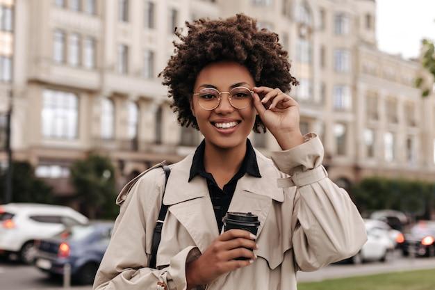 Mulher alegre, feliz, morena, encaracolada, com sobretudo bege, coloca os óculos redondos e segura a xícara de café do lado de fora
