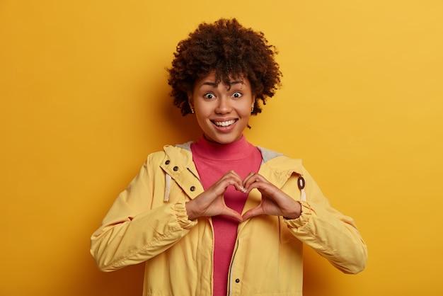 Mulher alegre, feminina, alegre, confessa estar apaixonada, molda o coração sobre o peito, expressa cuidado, diz