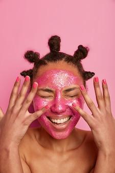 Mulher alegre fica nua, mostra uma manicure perfeita, sorri amplamente, aplica máscara facial rosa para efeito de rejuvenescimento, tem pãezinhos na cabeça, passa muito tempo sozinha, quer ficar sempre bonita