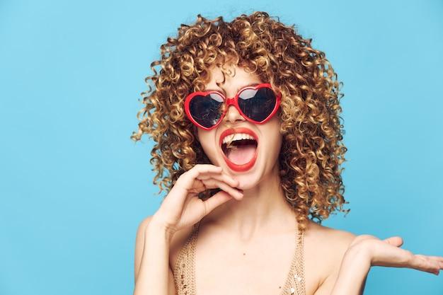 Mulher alegre glamour em um azul, óculos de sol da moda e estúdio