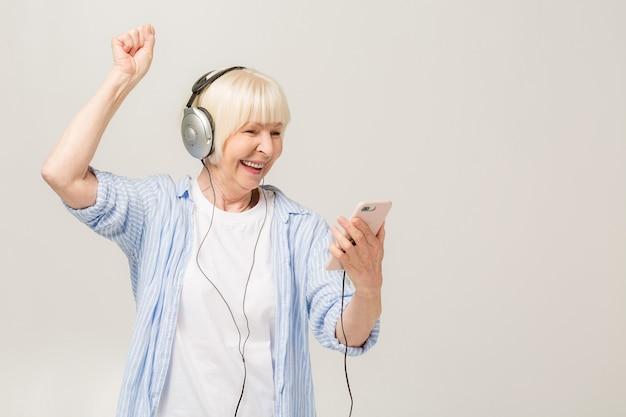 Mulher alegre idosa com fones de ouvido, ouvindo música em um telefone isolado no fundo branco.
