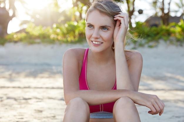 Mulher alegre jovem esguia em roupas esportivas, descansa após o exercício de treinamento de ioga, melhora a forma do corpo no verão, gosta do nascer do sol de manhã cedo. mulher em boa forma física gosta de esporte