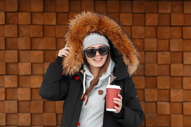 Mulher alegre jovem hippie com chapéu de malha vintage em óculos de sol em uma jaqueta de inverno com pele está de pé e segurando nas mãos um copo vermelho com café quente perto de uma parede de madeira. garota feliz e alegre.