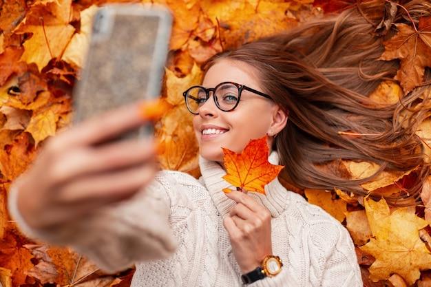 Mulher alegre jovem hippie com uma camisola de óculos com um lindo sorriso segura uma folha laranja perto do rosto e faz uma selfie. garota feliz se fotografa deitada na folhagem de outono em um parque.