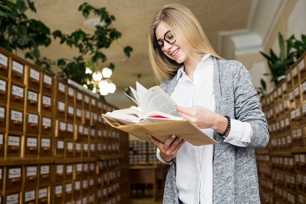 Mulher alegre lançando páginas do livro
