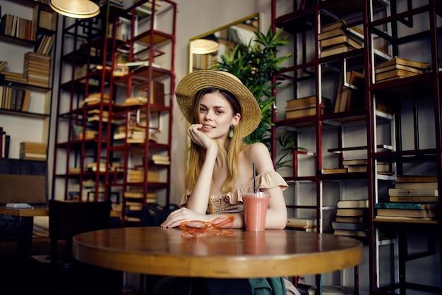 Mulher alegre lendo um livro no estilo café