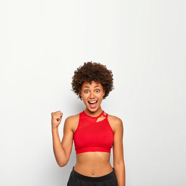 Mulher alegre levanta o punho cerrado, aplaude algo, gesticula com triunfo, tem uma figura perfeita, usa blusa vermelha, posa contra um fundo branco, espaço em branco acima