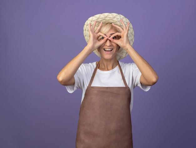Mulher alegre, loira de meia-idade, jardineira, de uniforme, usando chapéu, olhando para a frente, fazendo gesto de olhar, usando as mãos como binóculos, isolados na parede roxa com espaço de cópia