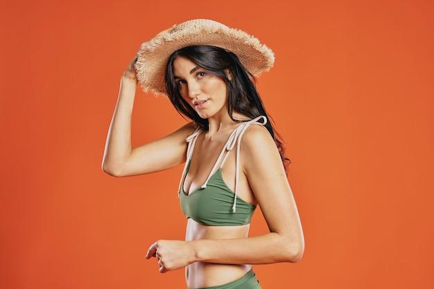 Mulher alegre maiô verde praia chapéu fundo vermelho glamour