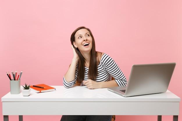 Mulher alegre, mantendo a mão na cabeça, olhando para cima pensando, sonhando, sente-se trabalhar na mesa branca com laptop pc contemporâneo isolado no fundo rosa pastel. conceito de carreira empresarial de realização. copie o espaço.