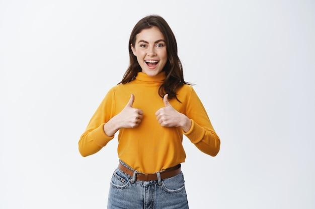 Mulher alegre mostrando feedback positivo com sinal de positivo, diga sim, concordo e aprovo um bom produto