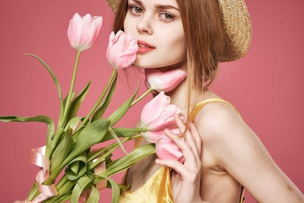 Mulher alegre mulher buquê de flores como um presente fundo rosa feriado