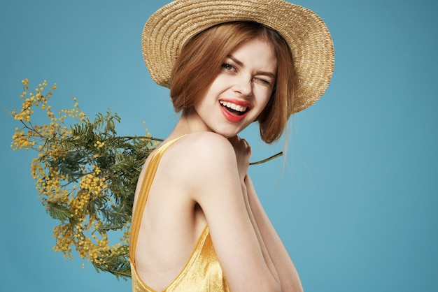 Mulher alegre na parede azul do estilo de vida do vestido dourado do chapéu.
