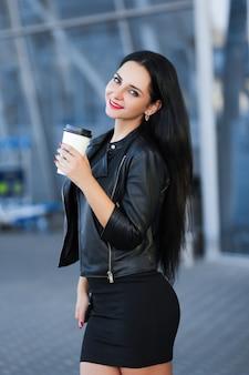 Mulher alegre na rua bebendo café da manhã no sol.