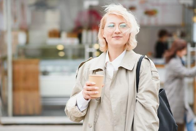 Mulher alegre na rua tomando café da manhã sob a luz do sol