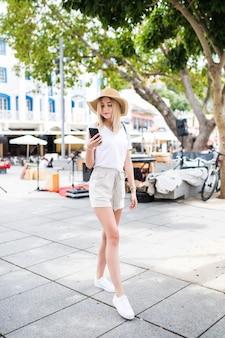 Mulher alegre na rua usa seu smartphone.