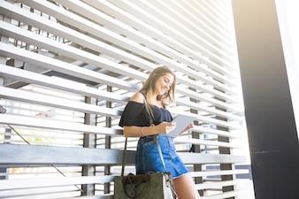 Mulher alegre navegando tablet perto da parede