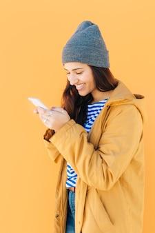 Mulher alegre no casaco amarelo usando telefone celular