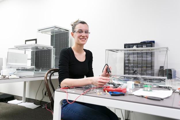 Mulher alegre no laboratório de técnicos