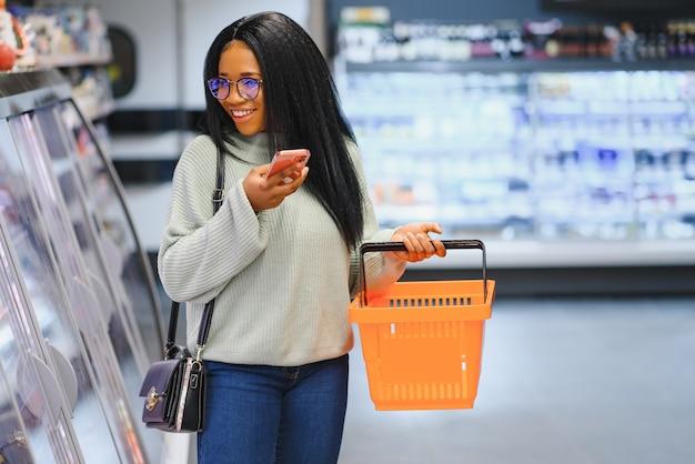 Mulher alegre no supermercado segurando uma cesta e sorrindo para a câmera