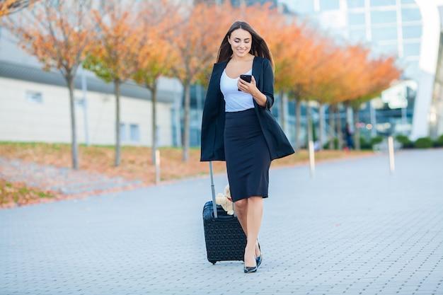 Mulher alegre nova com uma mala de viagem. o conceito de viagem, trabalho, estilo de vida