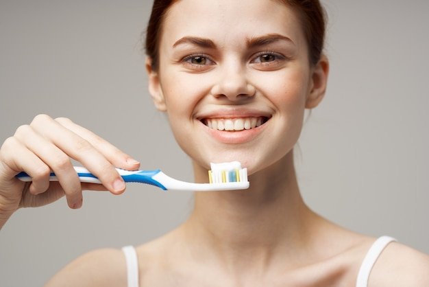 Mulher alegre, pasta de dente escovando os dentes saúde bucal luz de fundo