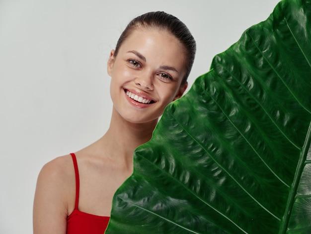 Mulher alegre pele limpa cosmetologia riso emoções folha de palmeira verde