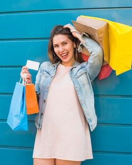 Mulher alegre permanente com sacos de compras e cartão de crédito