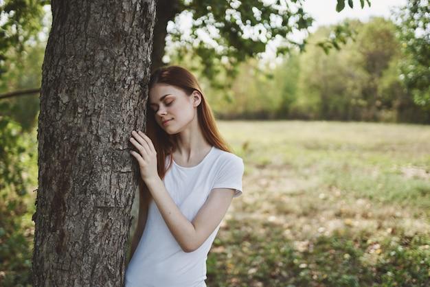 Mulher alegre perto da árvore natureza sol jornada pela liberdade