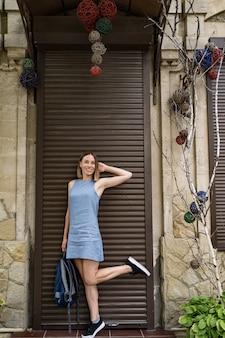Mulher alegre posando e segurando uma mochila nas mãos, apoiada em uma perna só em um vestido azul