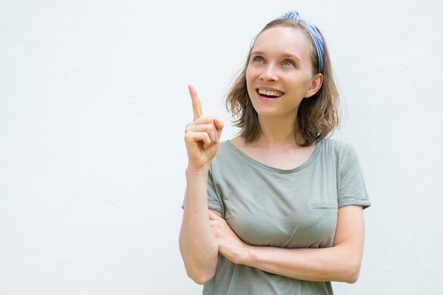 Mulher alegre positiva em roupas de verão, apontando para cima