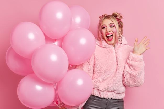 Mulher alegre positiva tem maquiagem brilhante, exclama algo alto, a palma levantada, vestida com roupas da moda, segura um monte de balões vem na festa de aniversário. conceito de férias e pessoas