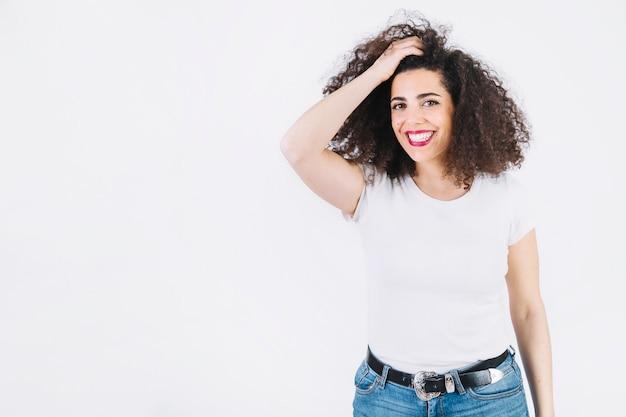 Mulher alegre que ajusta o cabelo