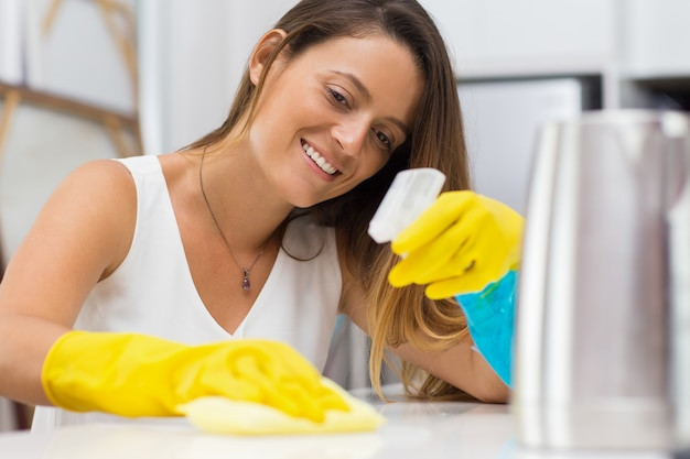 Mulher alegre que limpa completamente a mesa
