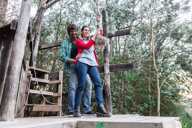Mulher alegre que prende uma corda no parque de aventura