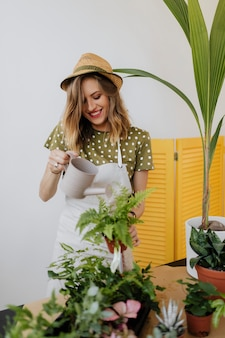 Mulher alegre regando as plantas de casa