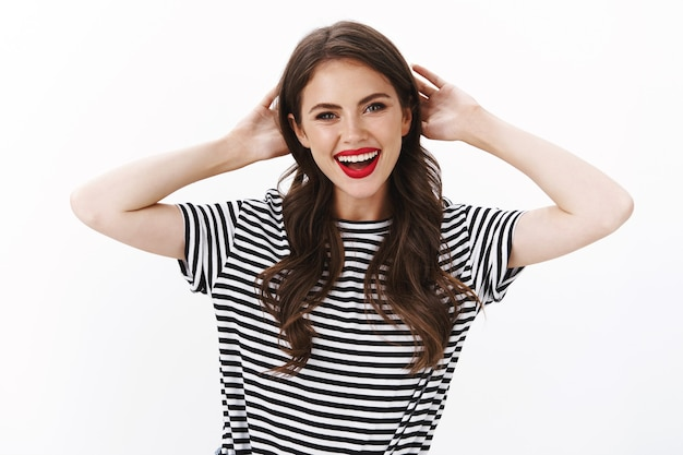 Mulher alegre, relaxada e despreocupada, atraente e sorridente com batom vermelho, camiseta listrada, mãos atrás da cabeça descansando, aproveite as férias de verão na piscina, se divertindo, em pé na parede branca