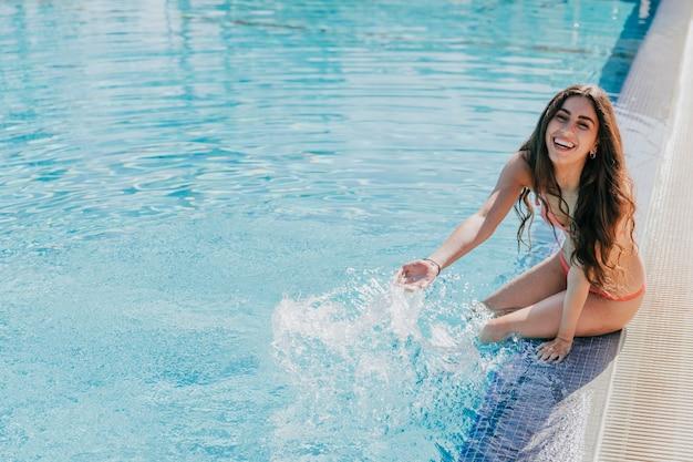 Mulher alegre relaxante ao lado da piscina