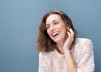 Mulher alegre rindo com a mão no cabelo
