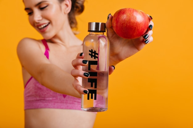 Mulher alegre saboreando maçã após o treino