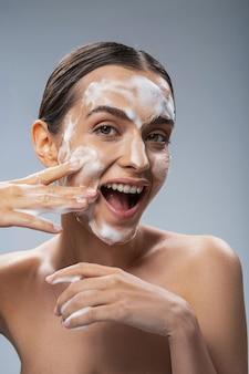 Mulher alegre se divertindo durante a limpeza do rosto