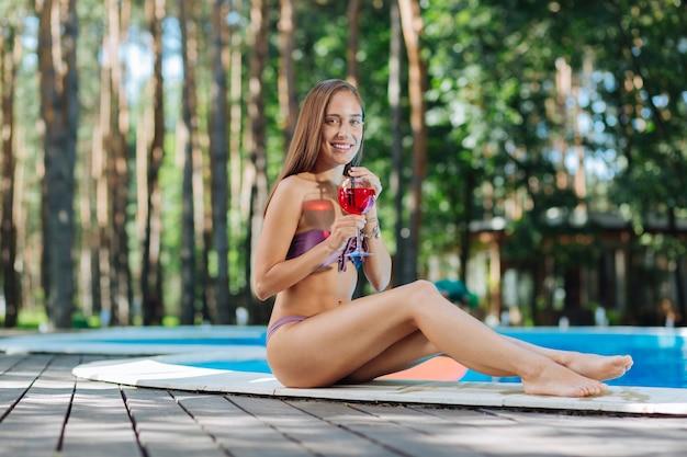 Mulher alegre se sentindo aliviada e descansada enquanto passa o dia de folga perto da piscina