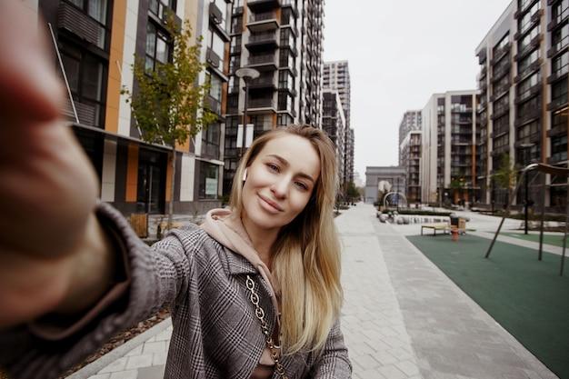 Mulher alegre segurando a câmera e tomando selfie. ela sorri e anda na rua. blocos de apartamentos em segundo plano. mulher loira elegante se divertindo lá fora. estilo de vida saudável.