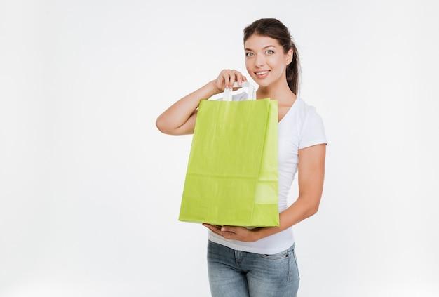 Mulher alegre segurando a compra depois de fazer compras e mostrando para a frente