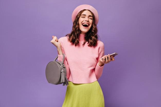 Mulher alegre segurando bolsa cinza e smartphone