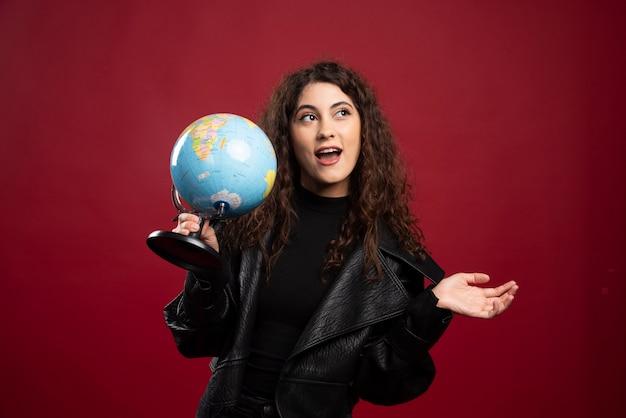 Mulher alegre segurando o globo.