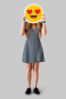 Mulher alegre segurando o ícone de emoticon