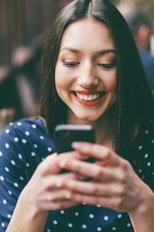 Mulher alegre segurando seu celular com ambas as mãos